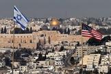 Bandeiras de Israel e dos EUA são vistas no telhado de um prédio em Jerusalém Oriental. (Foto: Ahmad Gharabli/AFP)
