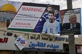 Pôster erguido na Cisjordânia pede boicote a Lionel Messi ao lado do retrato do presidente da Autoridade Palestina, Mahmoud Abbas. (Foto: AFP/Hazem Bader)