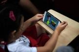 Criança assiste vídeo qualquer do Youtube em smartphone. (Foto: The Straits Times)
