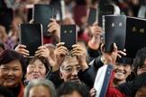 Cristãos Chineses mostram suas Bíblias em culto. (Foto: Bible Society - Australia)
