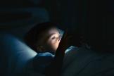 Imagem ilustrativa de menino deitado na cama com o celular. (Foto: iStock/Getty Images)