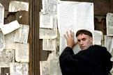 """Cena do filme """"Lutero"""", em que o personagem vive o tão citado episódio, no qual ele prega uma folha com as 95 teses da Reforma Protestante na porta de uma igreja. (Imagem: Youtube / Reprodução)"""