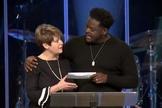 O pastor Derwin Gray entrega doação para Julie Walters, do Centro de Enriquecimento das Mulheres. (Foto: Reprodução/Facebook)