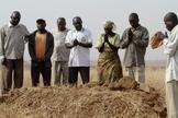 Pessoas se reúnem ao redor de uma sepultura, onde três parentes assassinados foram enterrados juntos, em Jos, no estado de Plateau, na Nigéria, em 28 de dezembro de 2011.  (Foto: Afolabi Sotunde/Reuters).