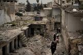 Mulheres caminham em um bairro fortemente danificado por ataques aéreos em Idlib, Síria, em 12 de março de 2020. (Foto: Felipe Dana / AP)