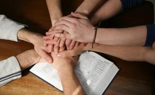 Mãos unidas sobre a Bíblia simbolizando a unidade da Igreja. (Foto: myocn.net)