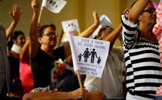 """Cristãos cubanos acenam bandeiras com a frase: """"Sou a favor do desenho original. A família como Deus a criou. Casamento entre homem e mulher"""". (Foto: Reuters/Alexandre Meneghini)"""