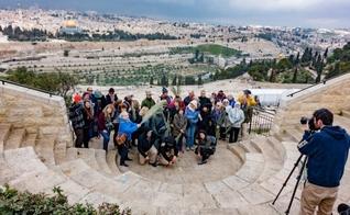 Grupo de turistas tira foto no Monte das Oliveiras, com a cidade velha de Jerusalém em segundo plano. (Foto: Shutterstock)