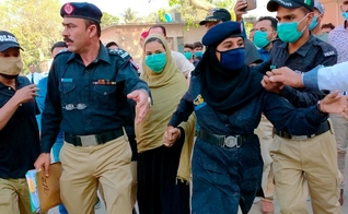 Policiais escoltam a adolescente paquistanesa Arzoo Raja, após sua aparição no Tribunal Superior de Sindh, em Karachi, Paquistão, no dia 3 de novembro de 2020. (Foto: AP Photo/Fareed Khan)