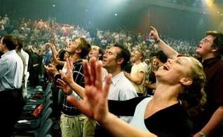 Pessoas participam de animado momento do culto na igreja.