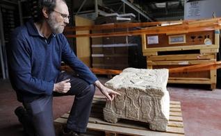 Gideon Avni, diretor da divisão arqueológica da Autoridade de Antiguidades, mostra a Pedra de Madalena. (Foto: Menahem Kahana/AFP)