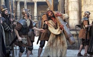Jesus (Jim Caviezel) carrega a cruz no filme A Paixão de Cristo. (Foto: Reprodução/Icon Productions)