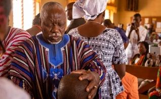 O Taraana, um dos sete anciãos do chefe supremo, ora sobre seus colegas diáconos durante a ordenação deles na Primeira Igreja Batista, Nalerigu. (Foto: Reprodução/IMB)