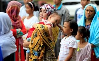 Mãe segura seu filho em meio ao caos instalado nas Filipinas, após cerco de terroristas. (Foto: Reuters)