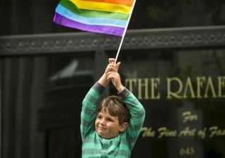 Garoto segura bandeira do movimento LGBT. (Foto: Reuters)