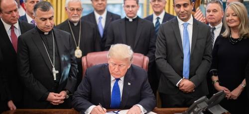 Donald Trump é cercado por líderes religiosos e legisladores no Salão Oval, ao assinar lei de ajuda humanitária. (Foto: Casa Branca/Shealah Craighead)