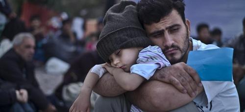 Refugiado sírio segura o filho nos braços em campo, na Turquia. (Foto:  AP/Lefteris Pitarakis)