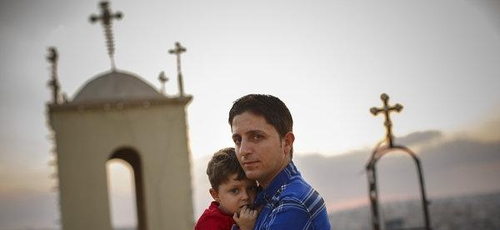 Homem cristão segurando seu filho, enquanto muitos de seus vizinhos fugiram da violência no Iraque. (Foto: Warrick Page/New York Times)