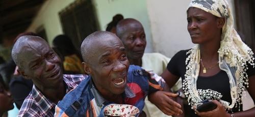 Liberiano chora enquanto o corpo de sua esposa é levado por uma equipe médica na África. (Foto: John Moore/Getty Images)