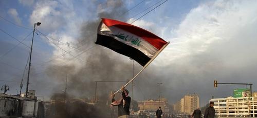 Manifestante acena a bandeira do Iraque enquanto fogo é ateado nas ruas próximas à Praça Tahrir, no Egito. (Foto: AP/Khalid Mohammed)