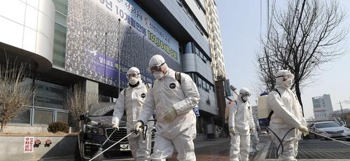 Trabalhadores com equipamento protetor usam desinfetante em spray contra o novo coronavírus em frente à igreja em Daegu, na Coreia do Sul, nesta quinta-feira (20). (Foto: Kim Jun-beom/Yonhap via AP)