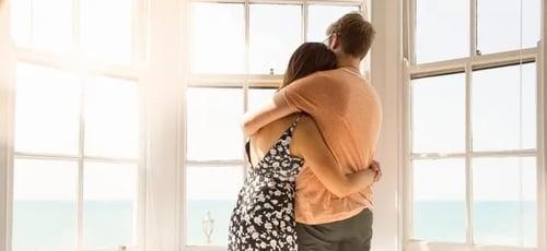 Casal jovem se abraça e olha pela janela da sala. Imagem ilustrativa. (Foto: Nick Doldin via Getty Images)
