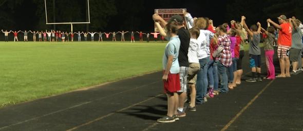 Estudantes reunidos em oração pela pequena Harper no campo de futebol da escola Lake City High School. (Foto: Twitter/Megan Viecelli)