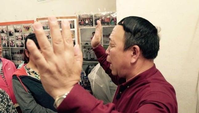 Pastor de igreja doméstica lidera momento de oração, na China. (Foto: ABC News)