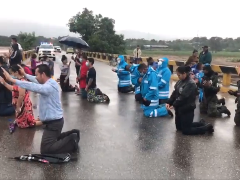 Policiais oram com cristãos em uma ponte sobre o rio Ulúa. (Foto: Policía Nacional de Honduras)