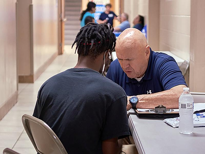 O voluntário Bob Filson aconselha um jovem em clínica médica no Tennessee. (Foto: Baptist and Reflector)