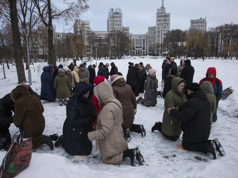 Ucranianos se ajoelham e oram na neve em praça da cidade de Kharkov (Foto: Reprodução/IMB)