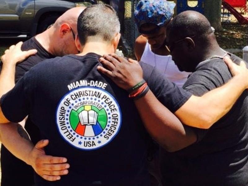 Policiais oram juntos e pelas pessoas nas ruas. (Foto: Reprodução/God Reports)