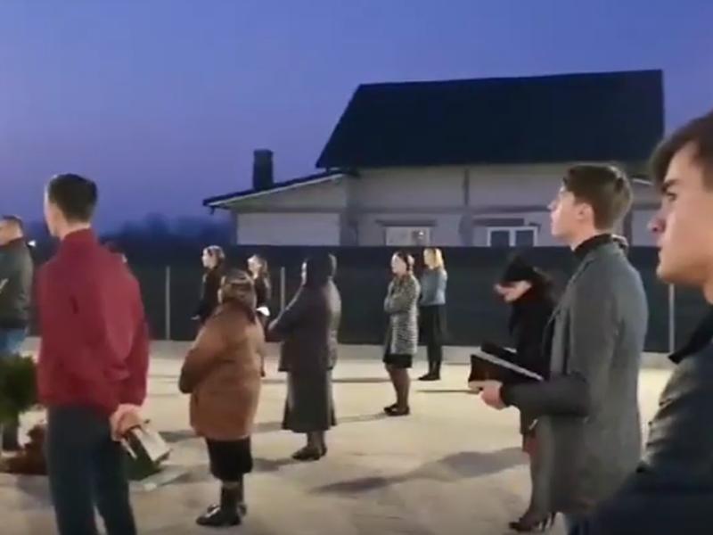 Membros da Igreja Cristã após o Evangelho de Sião, na vila de Prelipca, reunidos no estacionamento. (Foto: Reprodução/YouTube)
