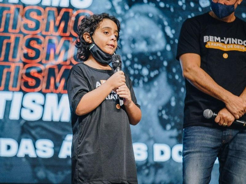 Arthur Ansuattigui, de 10 anos, conta testemunho ao lado do pastor Josué Valandro Jr. (Foto: Igreja Batista Atitude)