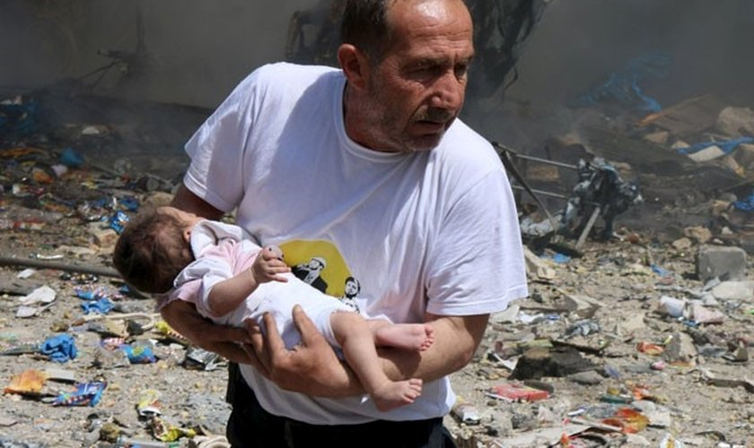 Homem segura bebê sobrevivente a bombardeio com barris explosivos em Aleppo. (Abdalrhman /Reuters)