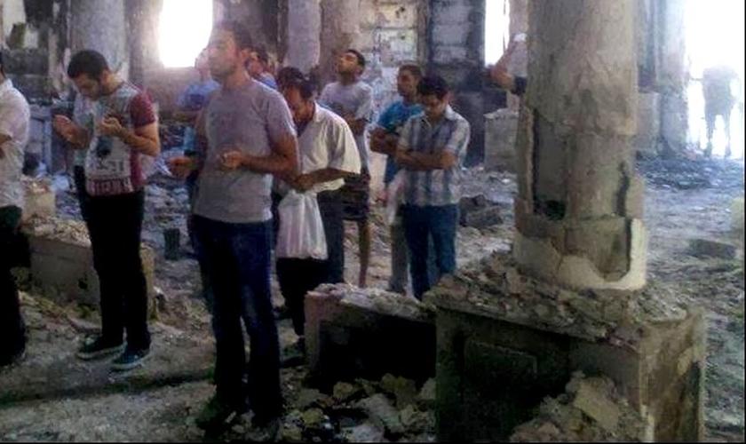 Cristãos oram dentro de templo em ruínas, na Síria.