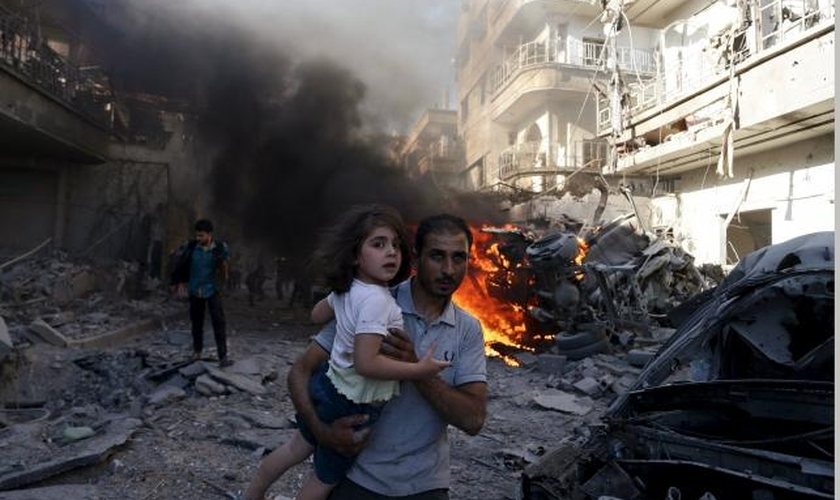 Homem leva uma garota nos braços, enquanto foge de um local atingido por ativistas, no bairro de Douma de Damasco (Síria), em agosto de 2015. (Foto: REUTERS/BASSAM KHABIEH)