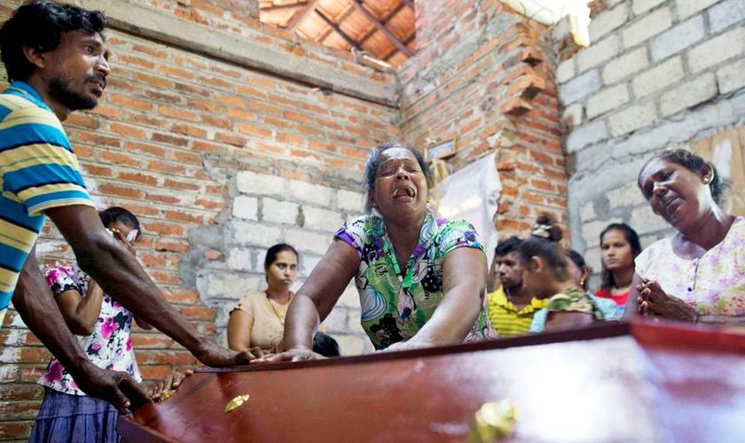 Lalitha chora sobre o caixão da sobrinha de 12 anos, Sneha Savindi, que foi vítima do ataque à igreja de St. Sebastian, no domingo de Páscoa, no Sri Lanka. (Foto: AP Photo/Gemunu Amarasinghe)