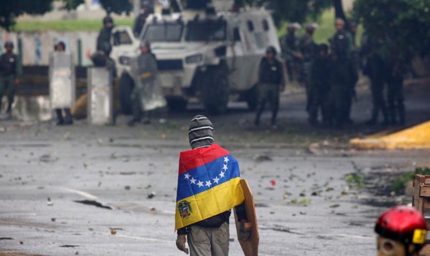 Manifestante de frente para as Forças Armadas em protesto contra Nicolás Maduro, na Venezuela. (Foto: Reuters/Carlos Garcia Rawlins)