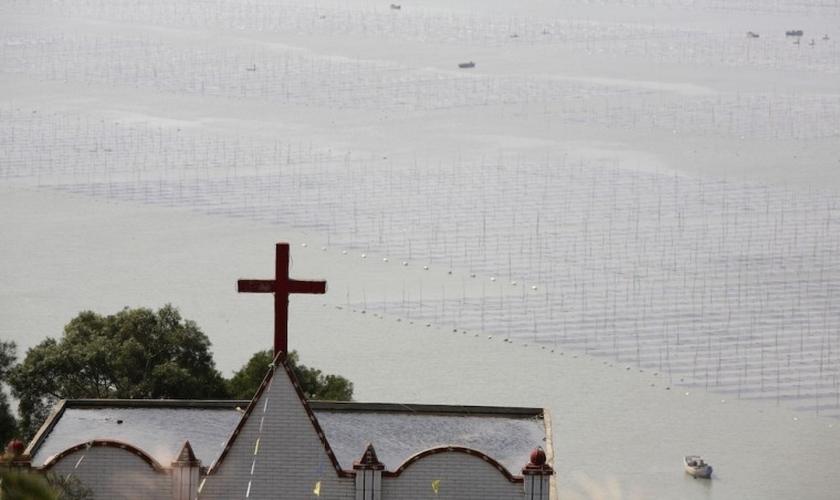 Uma igreja é vista ao lado de uma fazenda de lavatório na vila de Gutong, no município de Sansha, no condado de Xiapu, na província de Fujian, China. (Foto: Getty Images/China Photos)