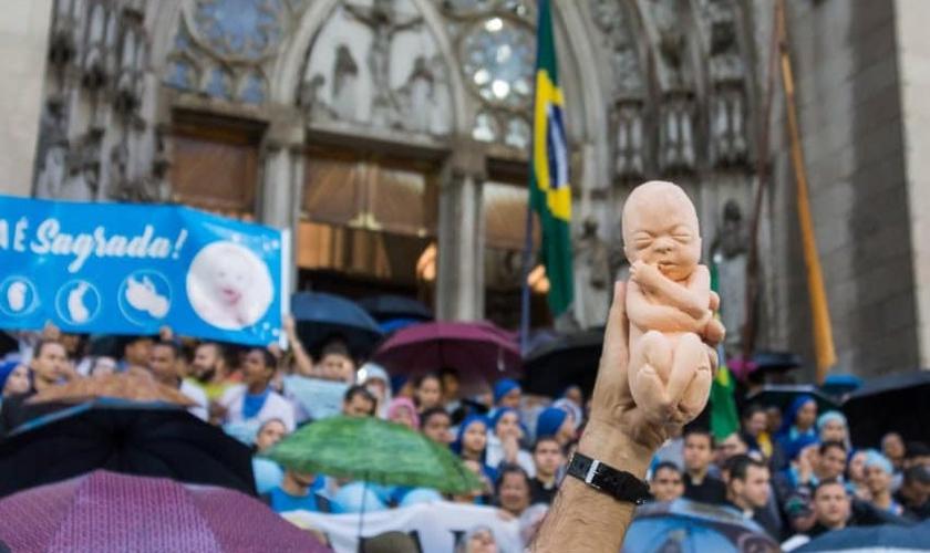 Manifestante pró-vida segura boneco de feto em protesto contra aborto. (Foto: Marcha Pela Vida Brasil)