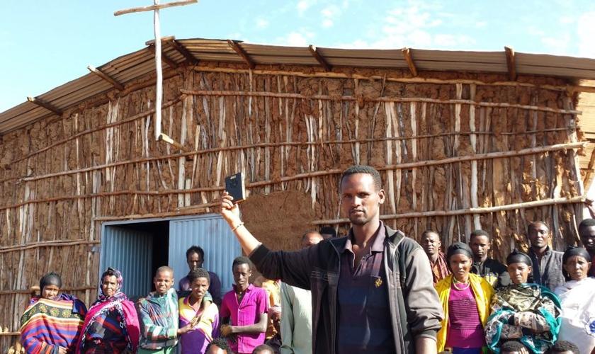 Em frente à igreja na África, cristãos seguram aparelho da Bíblia em áudio. (Foto: GHI)