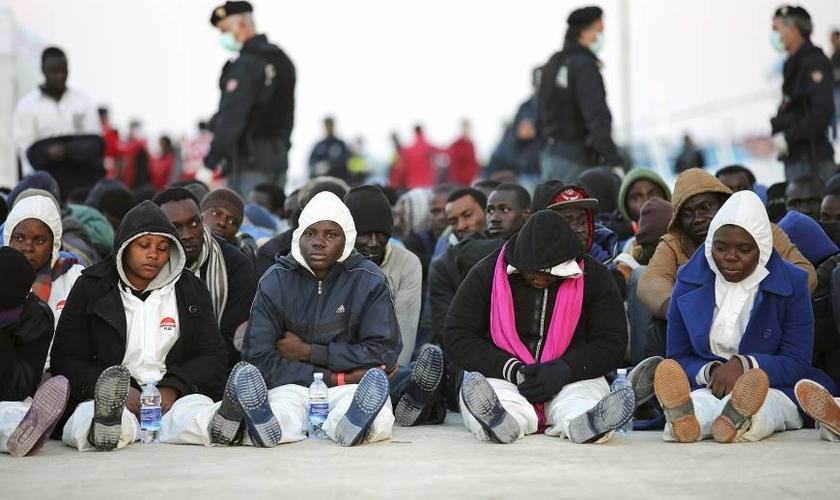 Migrantes descansam depois de desembarcarem no porto siciliano de Augusta. (Reuters/Antonio Parrinello)