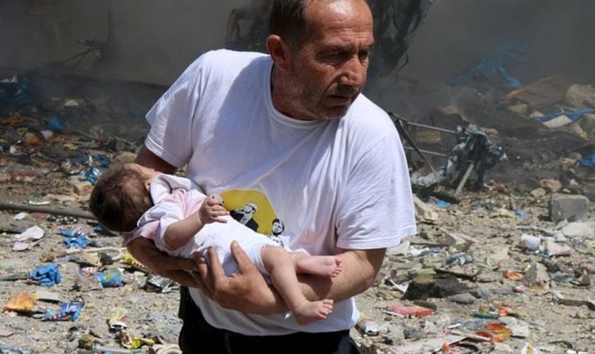 Homem segura bebê que sobreviveu a bombardeio com barris explosivos em Aleppo.