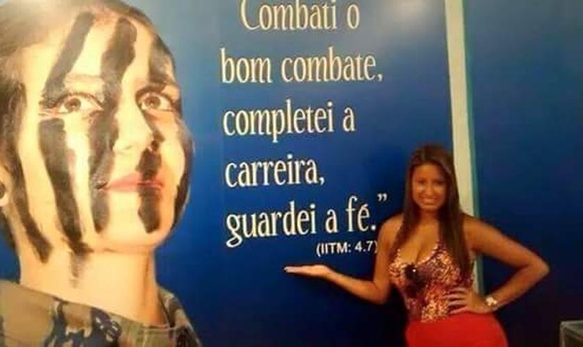 """Drielle diante de mural com versículo: """"Combati o bom combate, completei a carreira, guardei a fé"""". (Jornal Atual Rio)"""