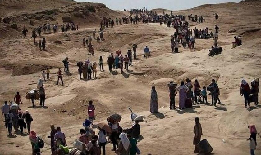 Cristãos fogem de cidade no Iraque, após terem seu território invadido por terroristas do Estado Islâmico.