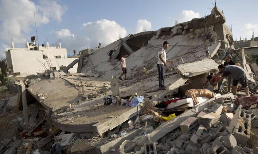 Palestinos tentam recuperar bens de um edifício destruído em um ataque israelense em Beit Lahya, norte da Faixa de Gaza