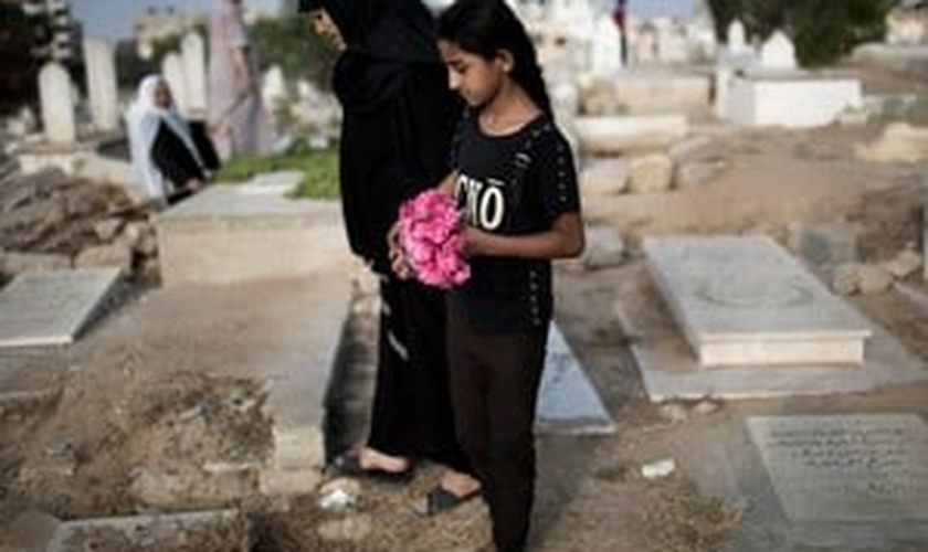 Mulher palestina e menina levam flores em um túmulo da família no feriado do fim do Ramadã (Eid al-Fitr) em Gaza. (