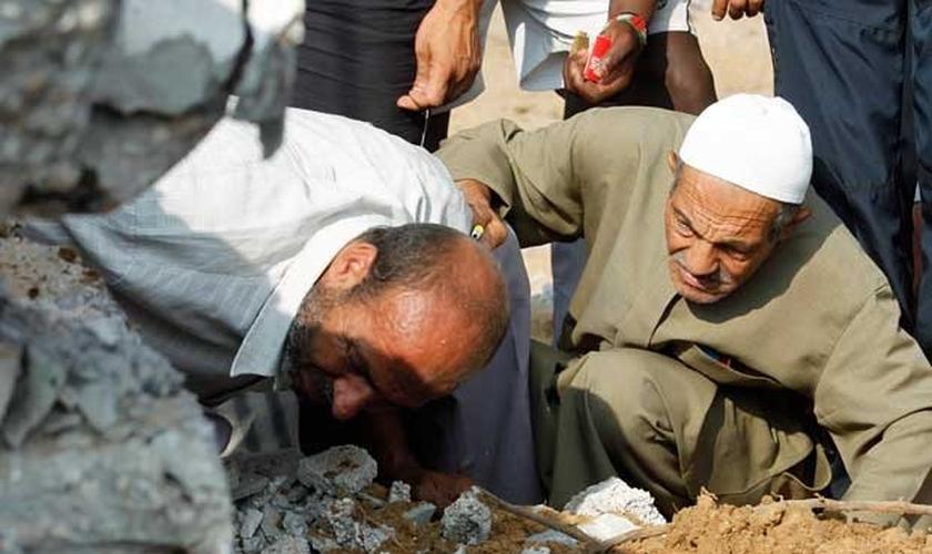 Equipes de resgate palestinas procuram vítimas em um prédio destruído por um ataque aéreo israelense em Rafah.