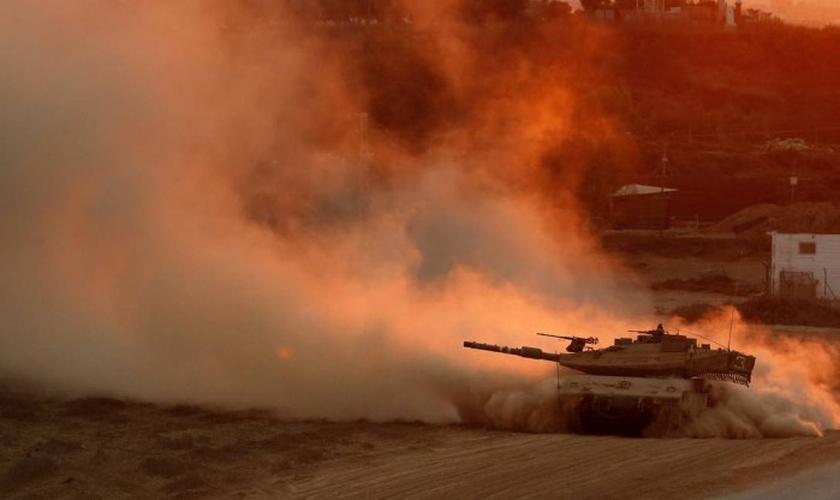 Um tanque israelense volta da Faixa de Gaza para uma base na fronteira israelense